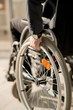Close-up of handicapped businessman putting hand on the wheel while sitting in the wheelchair