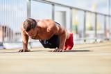 Athletic man doing push up exercise while training outdoors - 243036032