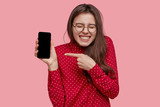 Optimistic Caucasian woman points at new smart phone for advertising, shows blank screen, likes multifunctional gadget, wears red shirt, poses over pink background. People and promotion concept - 243048679