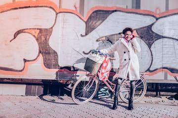 Cute international woman posing on camera in coat