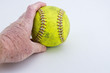 older male hand holding old use softball on white background