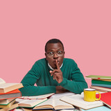 Photo of African American male bachelor keeps fore finger on lips, asks not making noise while studying, wears green sweater, drinks hot beverage, poses against pink wall with blank space above - 243057445