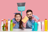 Positive two people look scrupulously at camera, hold broom and sponge, sit at desktop with cleaning supplies, notice object for cleaning, isolated against pink background. Tidying up concept - 243062626