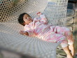 Little Asian baby girl, 36 months old, comfortably lying down on a hammock with the morning sunlight