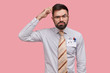 Hesitant unsure male designer scratches head and looks with serious expression, thinks about new sketh, wears formal shirt, has pens and pencil in pocket, models over pink background, finds decision