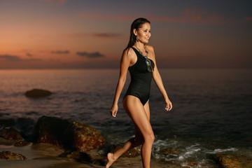Summer Beach Style. Woman In Black Swimsuit Walking At Sea Coast © puhhha