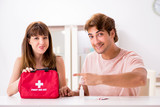 Young family getting treatment with first aid kit - 243078471