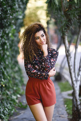 Beautiful young arabic woman with black curly hairstyle. © javiindy