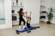 Leinwandbild Motiv Fit girls preparing legs workout. Leg stretching exercise fitness woman doing warm-up, hamstring muscles stretch standing at home.