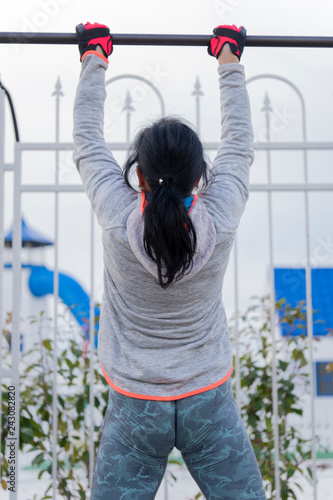 A woman pulls up on the horizontal bar