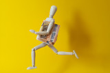 Wooden mannequiny running with a stack of banknotes. Economy. - 243091034