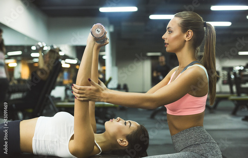 Leinwanddruck Bild Personal instructor helping woman with chest workout
