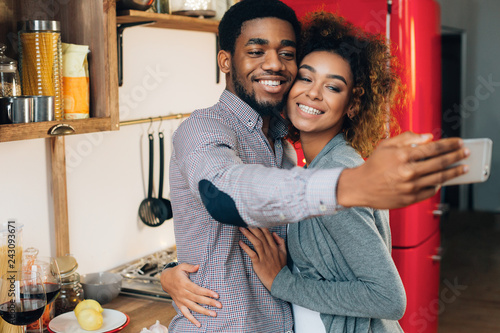 African-american couple taking selfie on smartphone in kitchen