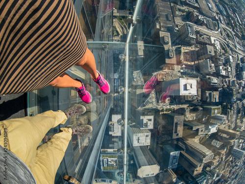 Leinwanddruck Bild Tourists posing on a glass floor