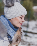 Woman playing with dog during winter - 243096892