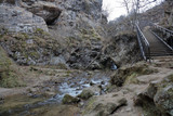 Small metal bridge with handrails over a mountain river in the gorge