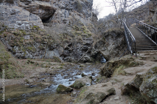 Foto Murales Small metal bridge with handrails over a mountain river in the gorge