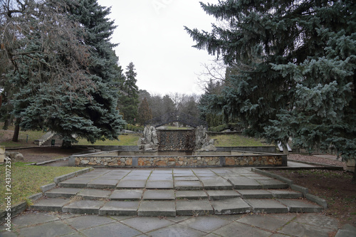 Old abandoned stone fountain in the autumn city park