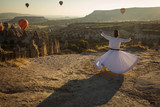 Dervish doing the retual in love valley of Cappadocia with balloons in background at sunrise. - 243110051