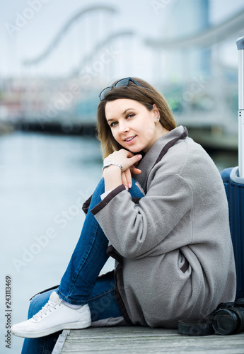 Leinwanddruck Bild woman with luggage  posing at quay and smiling