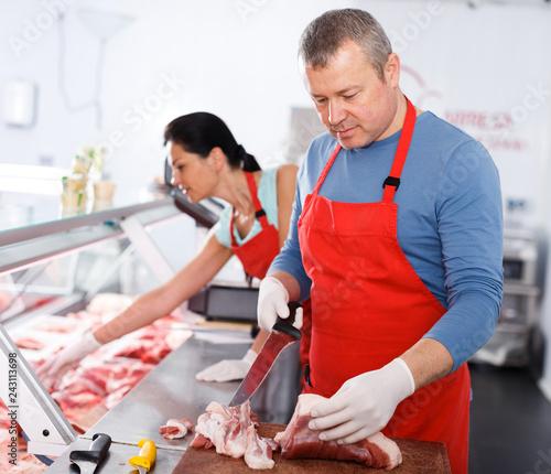Leinwanddruck Bild Man and girl seller working in butcher's shop