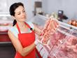 Leinwanddruck Bild - Glad young seller demonstrating meat in shop