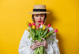 Fototapeta Tulipany - Beautiful woman in white shirt and hat with fresh springtime tulips on yellow background © Masson