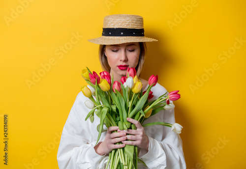 Beautiful woman in white shirt and hat with fresh springtime tulips on yellow background