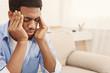 Leinwandbild Motiv African-american man suffering from headache at home