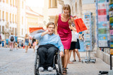 Woman and man in wheelchair with shopping bags in town - 243115290