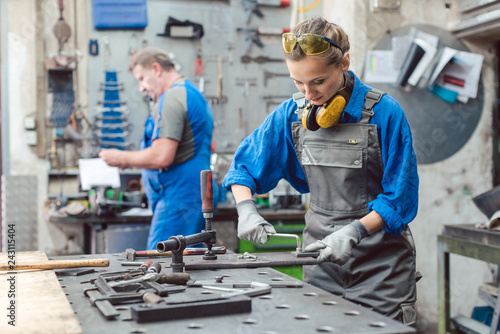 Leinwanddruck Bild Man and woman working together in metal workshop with their tools