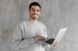 Portrait of young man in gray sweatshirt standing against textured wall, holding laptop and watching media with happy smile