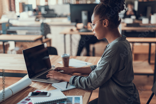 Charming afro american girl in glasses using laptop at work