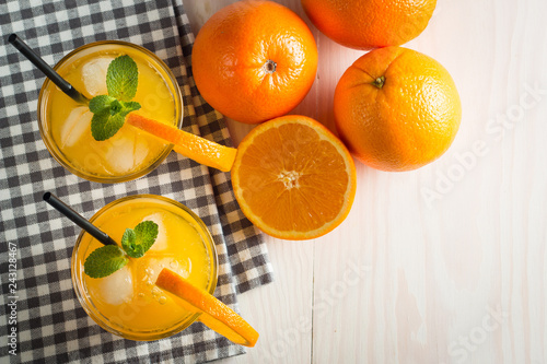 Photo of fresh orange juice in the glass jar. Summer healthy organic drink concept. Cold beverages with ice and orange fruits.