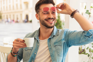 curious and smiling casual man fixing sunglasses drinks coffee