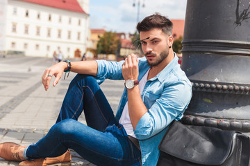 young casual man resting near pole in city holds sunglasses