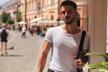 portrait of attractive casual man with red sunglasses standing