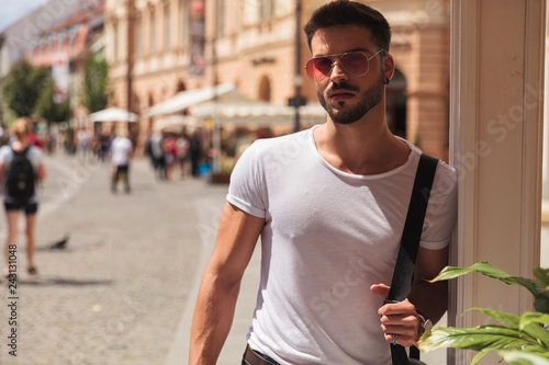 Leinwandbild Motiv portrait of attractive casual man with red sunglasses standing