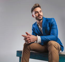 curious smart casual man sitting on blue wood bench and praying
