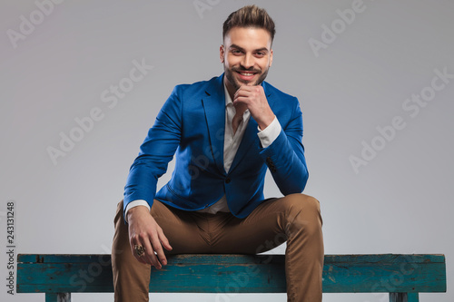 pensive and happy smart casual man in blue suit sitting - 243131248