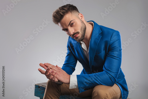 Leinwandbild Motiv sexy smart casual man sitting and holding palms together