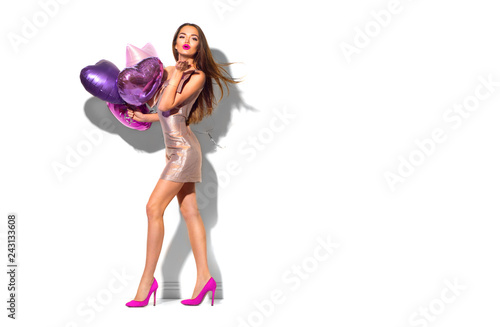Beauty fashion model party girl with heart shaped air balloons posing. Beautiful young brunette woman full length portrait isolated on white
