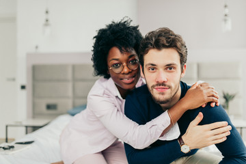 Happy African american girl embracing her handsome caucasian boyfriend while sitting on bed in bedroom with modern grey colored interior and big windows.