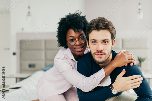 Leinwandbild Motiv Happy African american girl embracing her handsome caucasian boyfriend while sitting on bed in bedroom with modern grey colored interior and big windows.