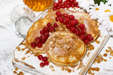 delicious pancakes with berries and honey on a white wooden board, top view - 243139294