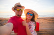 Travel and holidays concept - Happy young couple in love takes selfie portrait on the beach - 243140212