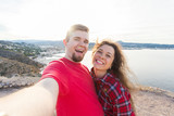 Travel, vacation and holiday concept - Beautiful couple having fun, taking selfie over beautiful landscape - 243140445