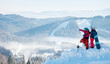 Two snowboarders - man and woman enjoying beautiful natural landscape, resting on top of the mountain on a sunny winter day at ski resort. Man pointing to the background copyspace lifestyle recreation