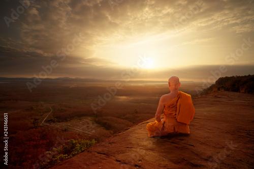 Leinwandbild Motiv Buddhist monk in meditation at beautiful sunset or sunrise background on high mountain