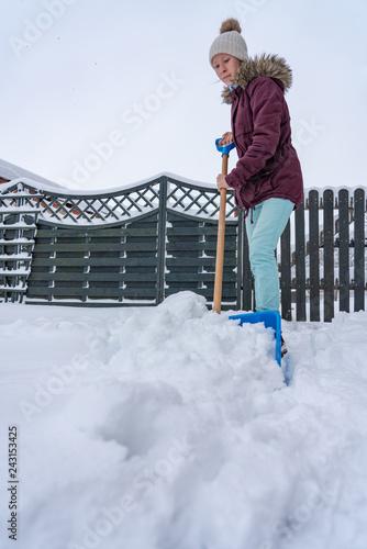 junges kaukasisches Mädchen räumt Schnee